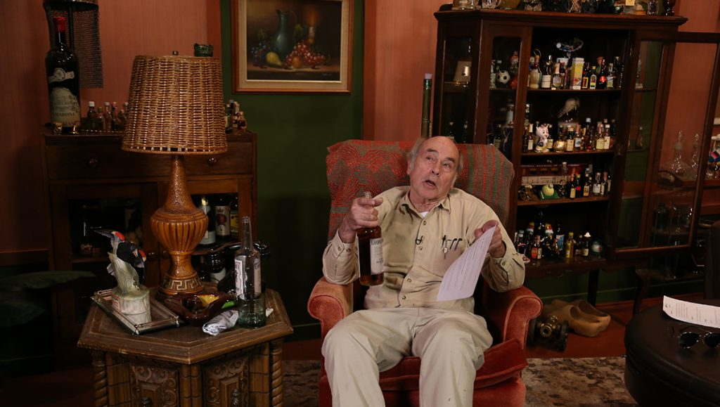 Lahey sits in his liquor chair with a bottle of liquor