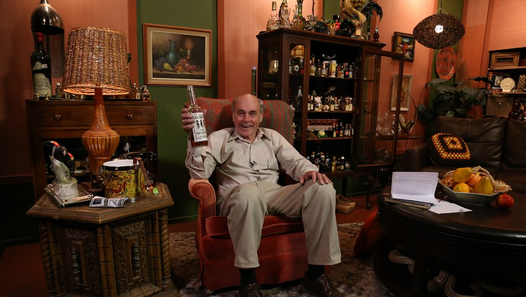 Lahey happily holds up a bottle of Liquormen's!