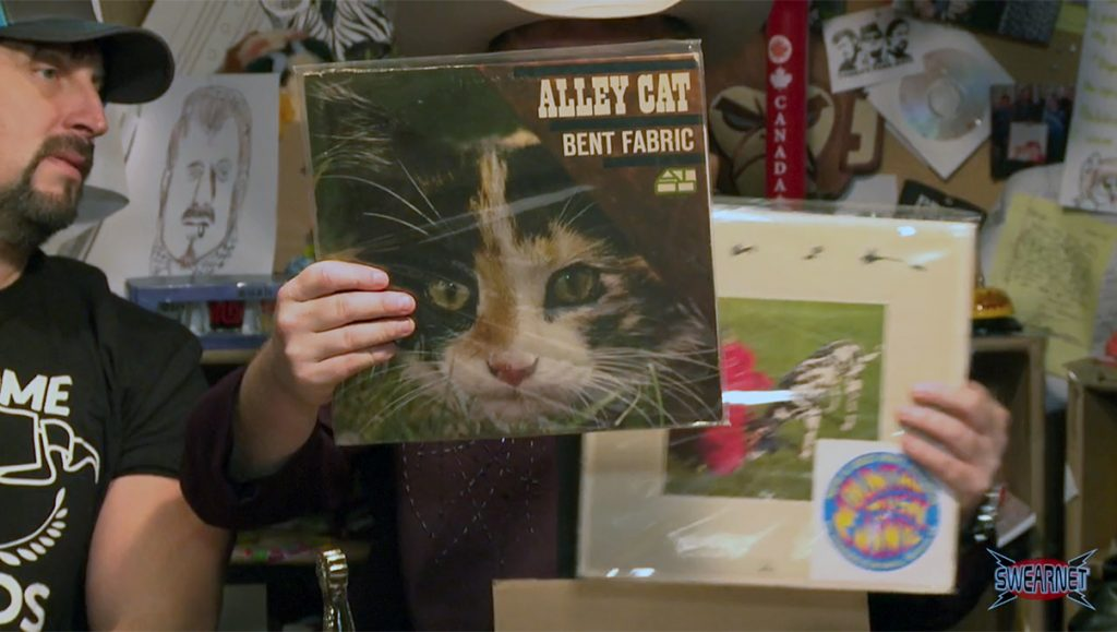 Mike Smith holds up an album called ALLEY CAT