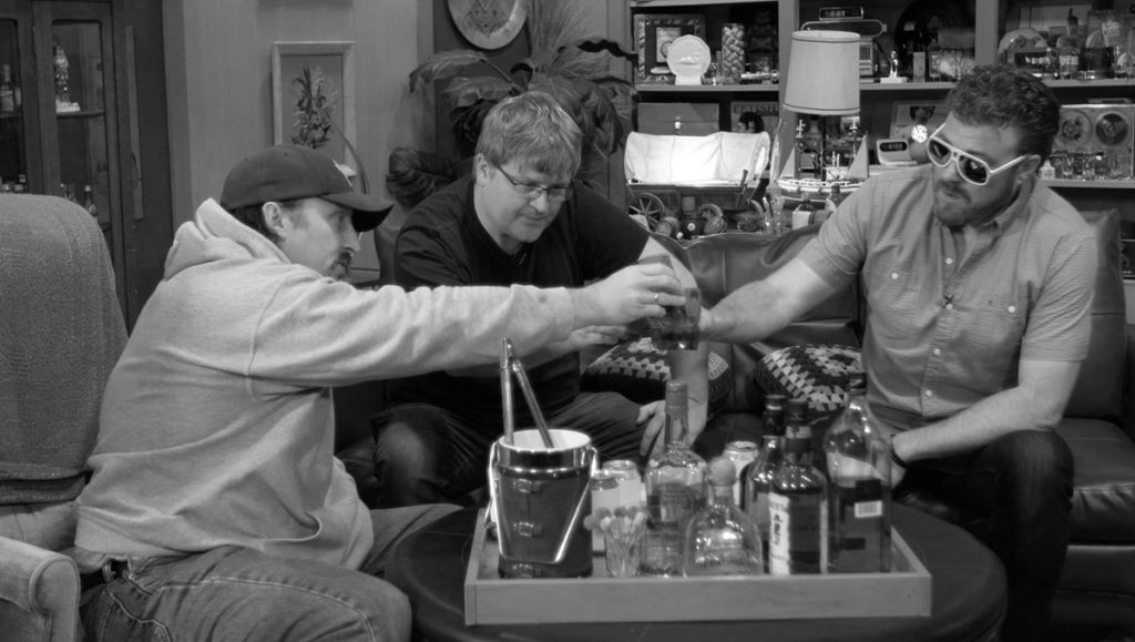JP, Mike, and Robb raise a glass to the memory of John Dunsworth